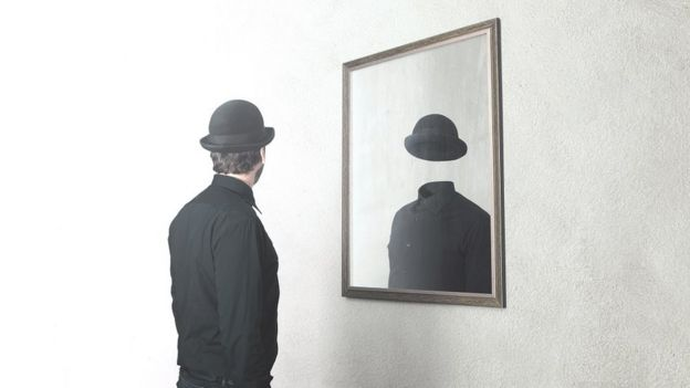 Conceptual photo of a man looking at himself in the mirror, in his reflection there is no face.