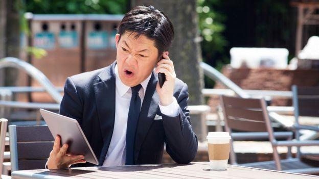 Homem falando ao celular com raiva