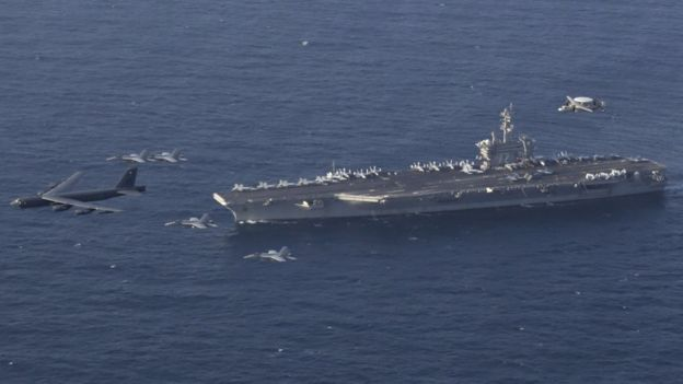 A handout photo made available by the US Navy shows the Abraham Lincoln Carrier Strike Group and a US Air Force B-52H Stratofortress, assigned to the 20th Expeditionary Bomb Squadron and part of the Bomber Task Force deployed to the region, conducting joint exercises in the US Central Command area of responsibility, in the Arabian Sea (1 June 2019)