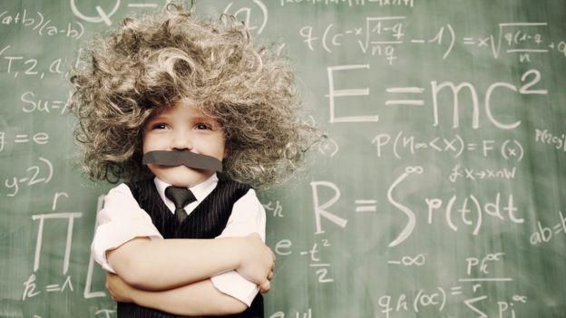 Niño y pizarra con ecuaciones