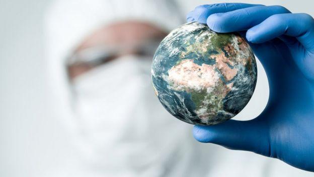 Homem segurando um globo terrestre