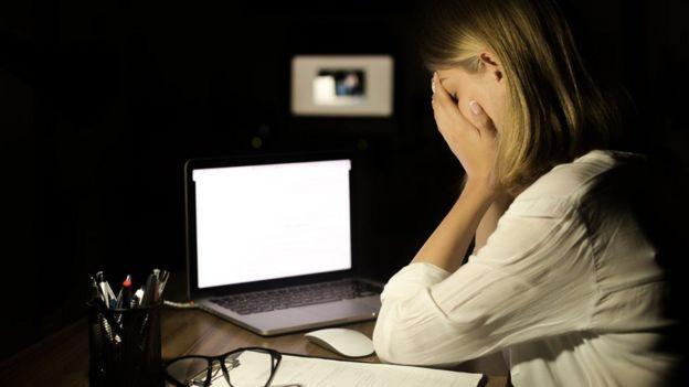 Mujer ante la pantalla de una computadora
