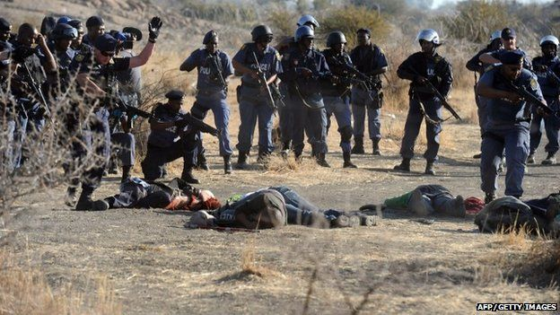 Police surrounding fallen miners after they opened fire during clashes near a platinum mine in Marikana.