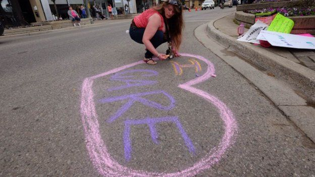 """A woman rights """"I care"""" in chalk"""