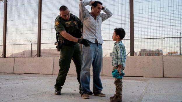 Un agente migratorio detiene a un hombre delante de un menor