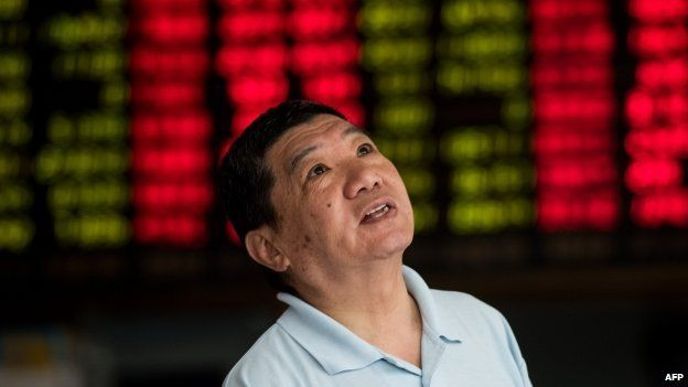 An investor monitors screens showing stock market movements at a brokerage house in Shanghai