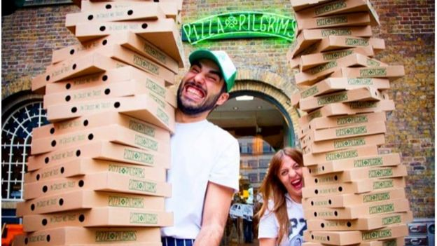 Personal de Pizza Pilgrims cargando cajas