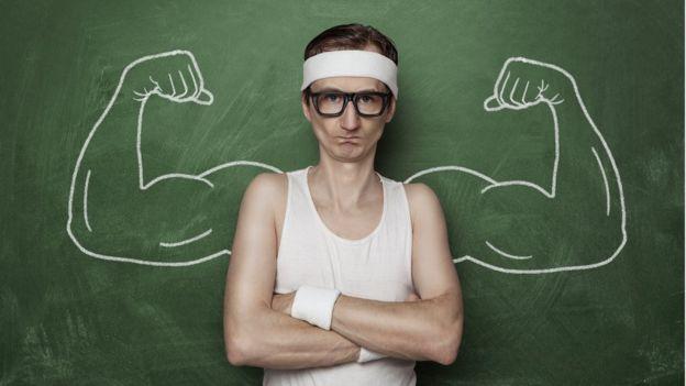 Homem diante de quadro com desenho de braços fortes