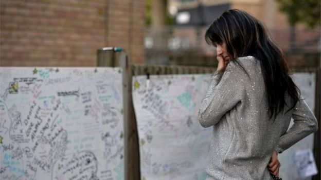 A Woman Reacts In Front Of Message Wall Near The Scene Fire That