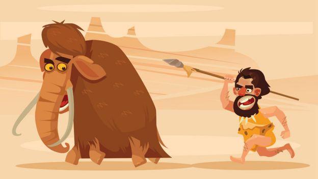 Um homem das cavernas perseguindo um mamute com uma lança