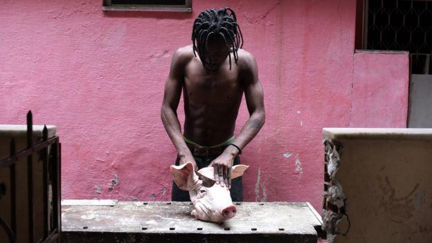 Ali Ngangu Ntela começa a desmembrar uma cabeça de porco cuja carne será usada no preparo de uma refeição