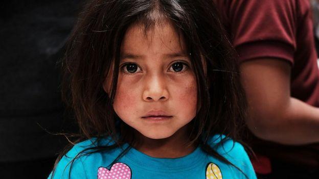 Una niña pequeña que migró junto a su familia mira fijamente a la cámara.