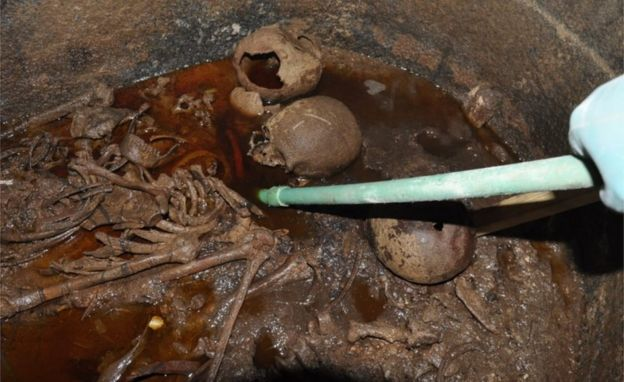 Three skeletons from the sarcophagus pictured submerged in red-coloured sewage water