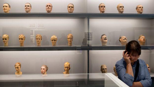 Mulher em exposição de rostos esculpidos