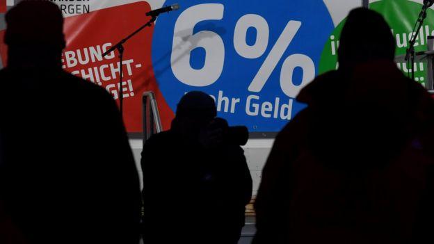 """Trabajadores de Airbus parados frente a un banderín que lee """"6% más en dinero"""""""
