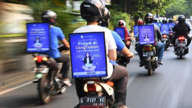 Pengendara ojek daring menggelar aksi konvoi sebagai sosialisasi layanan aplikasi UangTeman di Surabaya, Jawa Timur, Kamis (18/10).