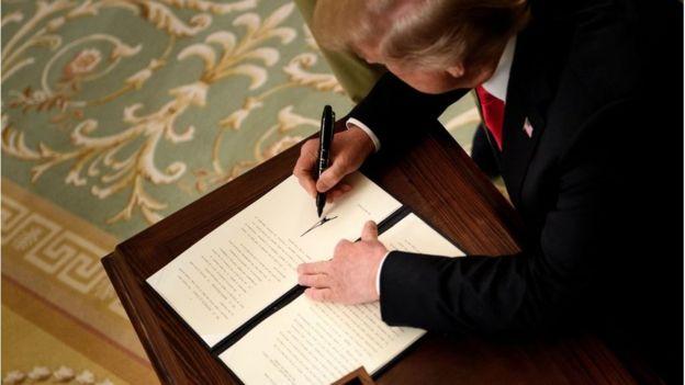 美国总统特朗普正在签署一项行政令。