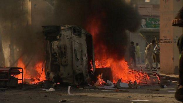 Un vehículo en llamas en una protesta en Kasur, Pakistán.