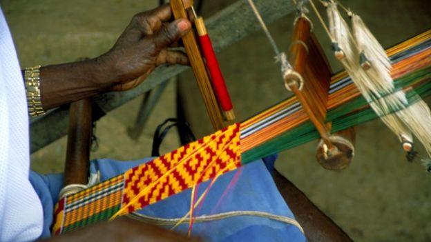 Person weaving kente