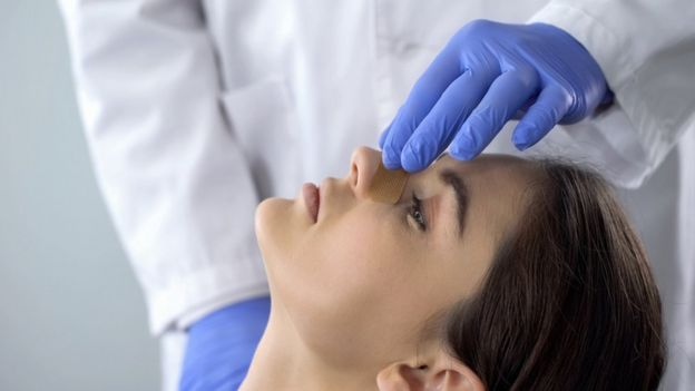 Mujer chequeándose la nariz con un especialista.