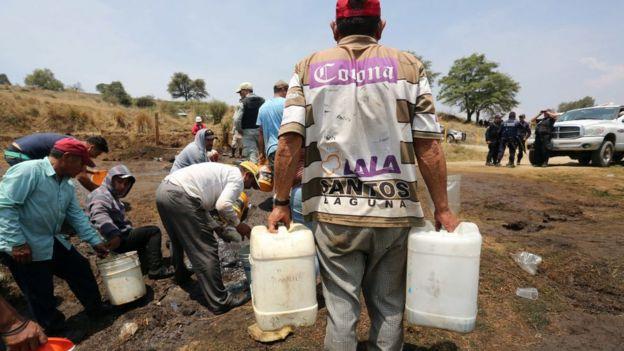 Residentes de Puebla recogen combustible de una fuga, con autorización de Pemex.
