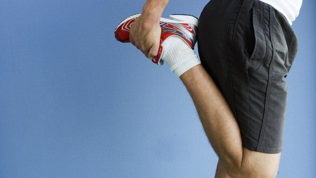 Man stretching leg muscle