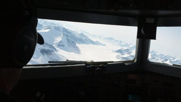 From the cockpit of the plane: a chain of snowy mountains with an ice-filled valley in between