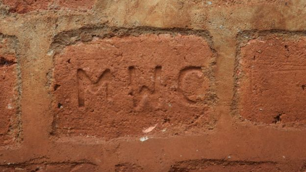 Brick with initials MWC on it