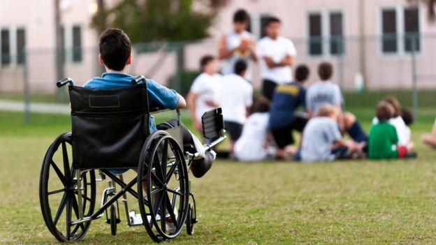 Un niño en silla de ruedas alejado de un grupo de jóvenes.