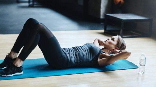 Mujer en posición de hacer abdominales
