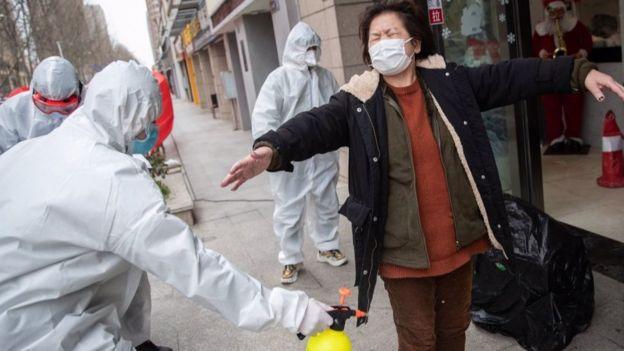 Волонтеры в Ухане опрыскивают женщину дезинфицирующим раствором