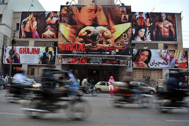 In this photograph taken on January 14, 2009 commuters pass a cinema displaying billboads advertising the Indian Bollywood film 'Ghajini' in Karachi. Just a year ago, the screening would not have been possible, as Pakistan had barred films from its rival neighbour for more than 40 years. Lifting the ban has helped revive Pakistan's suffering cinemas, luring film buffs away from the flat-screen televisions in their living rooms and into the movie houses.