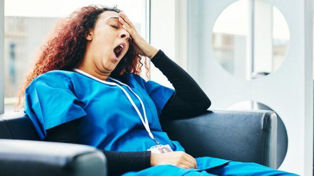 Una mujer enfermera bosteza.