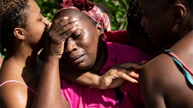A woman in the Bahamas holds her head in her hands as she is greeted by loved ones following Hurricane Dorian