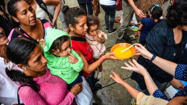 Personas esperan plato de comida en Caracas
