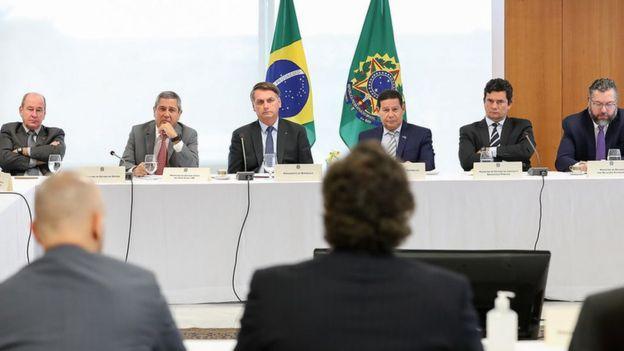Bolsonaro sentado ao lado de vice-presidente e ministros