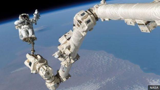 การออกเดินในอวกาศ (Spacewalk)โดยยึดตัวเองไว้กับแขนกลซึ่งเป็นส่วนหนึ่งของสถานีอวกาศ