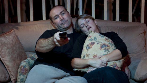 Homme et femme s'endormir en regardant la télévision sur le canapé