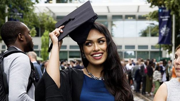 Bhasha in a graduation cap and gown