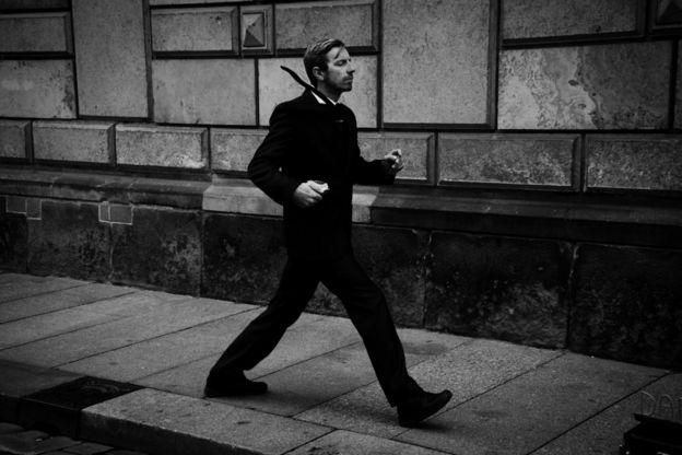 أحد فناني الشوارع يؤدي عرضا ويبدو متحركا مع أنه في الواقع ساكنا غير متحرك