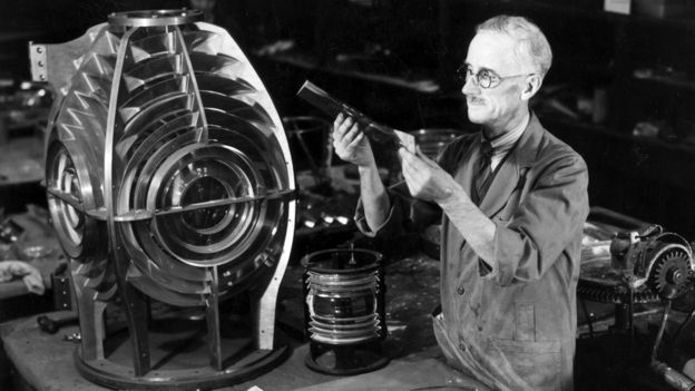 A worker assembles prisms to form the lighthouse lens