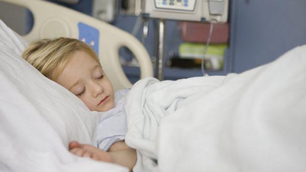 Niño en una cama de hospital.