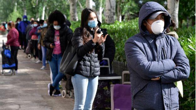 Cola de personas con mascarilla y carritos para llevar alimentos en Madrid