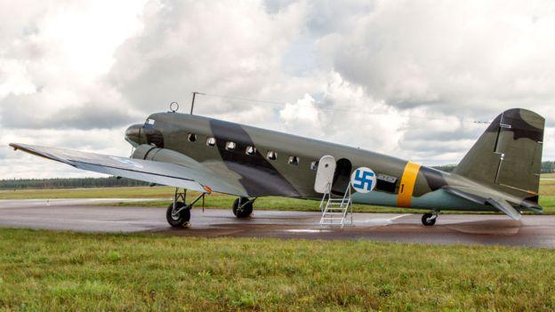 Avião da Força Aérea finlandesa restaurado com uma suástica azul, em pista de aeroporto