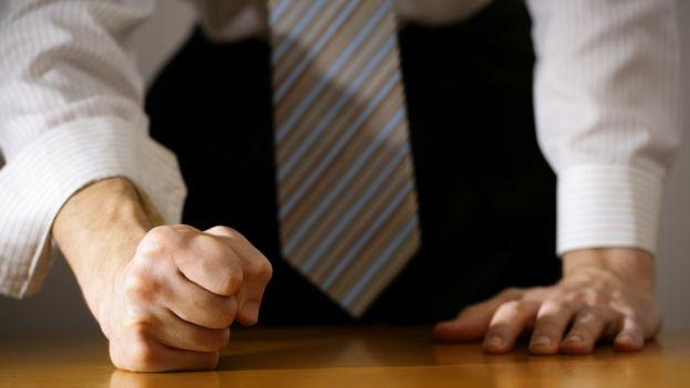 Een man met zijn vuisten balde aan tafel.