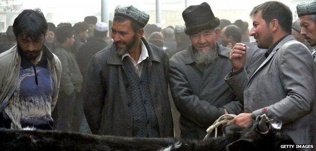 Uighur men gather at a bazaar to sell their live sheep in the Xinjiang region (7 November 2013)