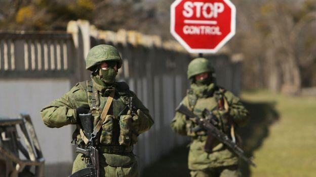 Dois soldados fardados com vestes verdes, armados e sem identificação na Crimeia