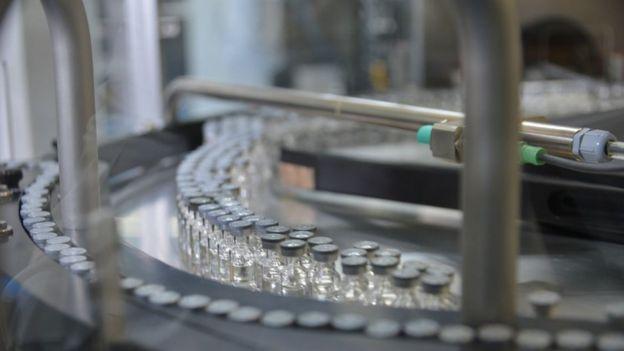 Linha de produção com frascos de vacina