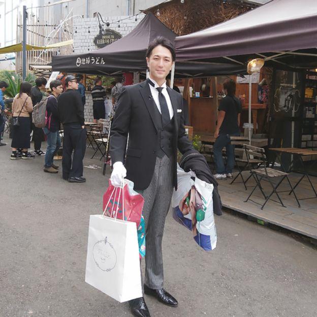 Yuichi Ishii vestido elegantemente de saco y chaleco negros, guantes blancos, cargando bolsas de compras