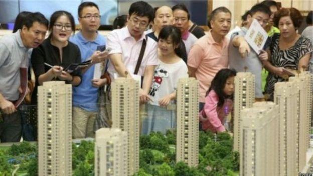 一群購房者在新樓盤的模型前進行諮詢。